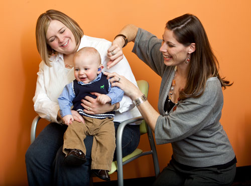 An audiologist fitting a baby with a hearing aid