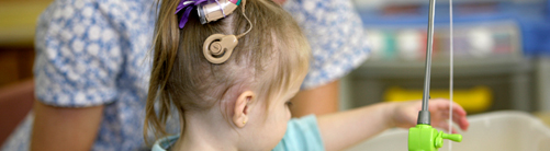 A girl with a cochlear implant, playing with a toy